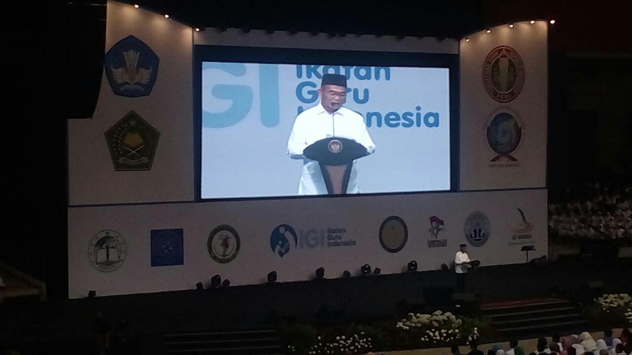Pidato menteri Pendidikan dan Kebudayaan dalam HGN dengan latar belakang Logo IGI.